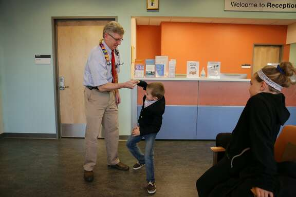 Rhett Krawitt (center) has a thumb war with Dr. Robert Goldsby (left), pediatric oncologist,  while his sister Annesley Krawitt (right) watches as Rhett and his family stop in for a visit at UCSF Benioff Children's Hospital on Wednesday, December 16, 2015 in San Francisco, Calif.