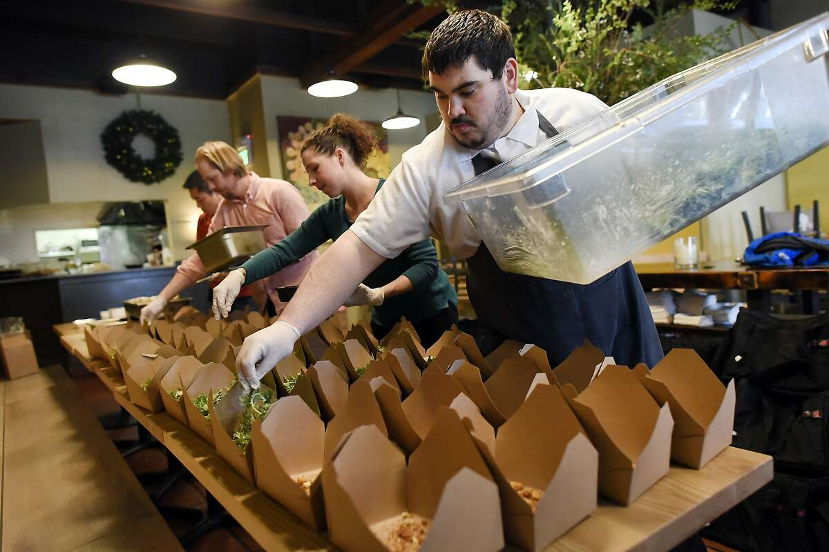 Corporate chef Dan Davidson, right, and co-owner Tai Ricci, co-owner Jason Kirmse, and Co-owner Jason Halverson prepare boxes of Fat Angel Kale Salads for pickup by food delivery service Uber Eats, at Stone's Throw restaurant in San Francisco, CA Wednesday, December 23, 2015.