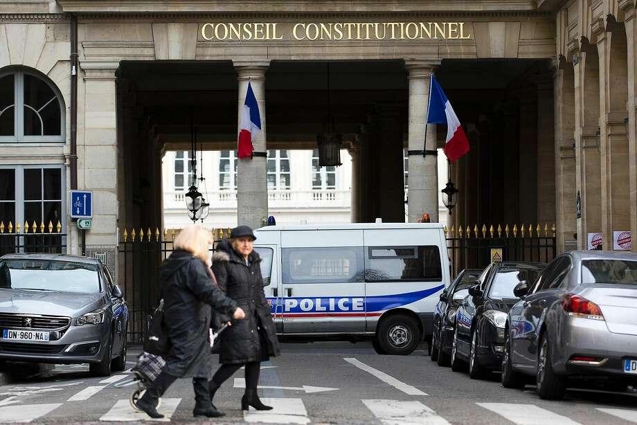 People walk past a police van outside the Constitutional Council in Paris, where the Cabinet backed proposals to prolong the current state of emergency beyond its three-month window. Photo: Kenzo Tribouillard, AFP / Getty Images