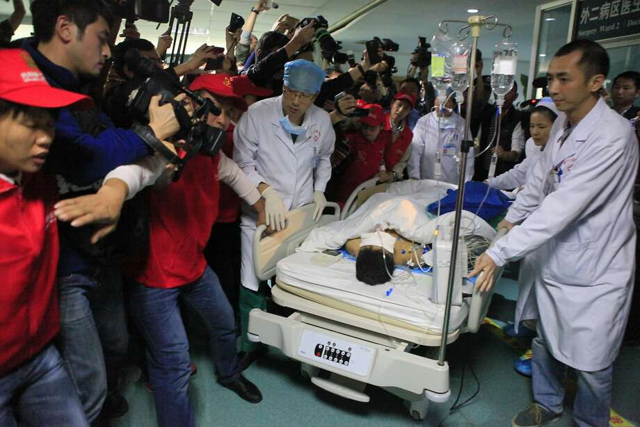 Medical staff move landslide survivor Tian Zeming following surgery in a hospital in Shenzhen in southern China's Guangdong province. He is in stable condition despite multiple fractures. Photo: Associated Press
