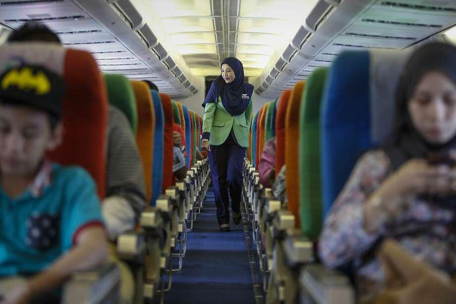A Rayani Air flight attendant walks down the aisle before departure at Kuala Lumpur airport. Photo: Joshua Paul, Associated Press