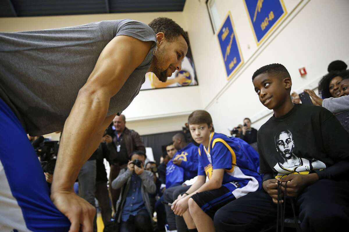 Make-A-Wish participants Qwavon Christian, 10, meets Stephen Curry after watching Golden State Warriors' shootaround at Warriors' practice facility in Oakland, Calif., on Wednesday, December 23, 2015.