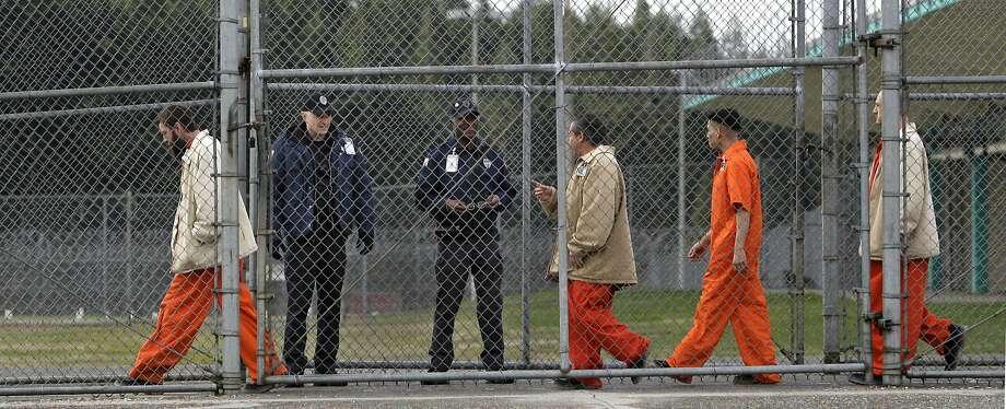 Washington state inmates walk past correctional officers at the Washington Corrections Center in Shelton, Wash. Photo: Elaine Thompson, Associated Press