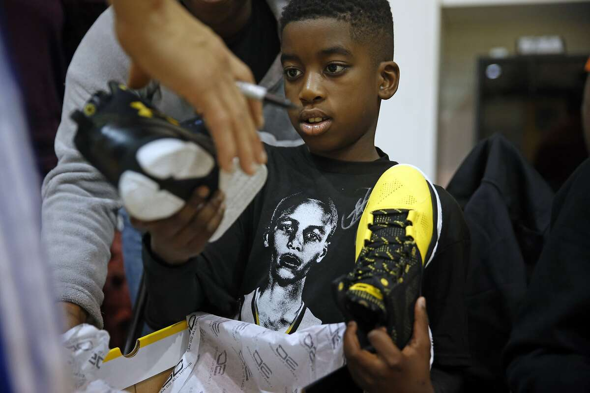 Make-A-Wish participants Qwavon Christian, 10, has his Under Armour shoes signed by Stephen Curry after watching Golden State Warriors' shootaround at Warriors' practice facility in Oakland, Calif., on Wednesday, December 23, 2015.