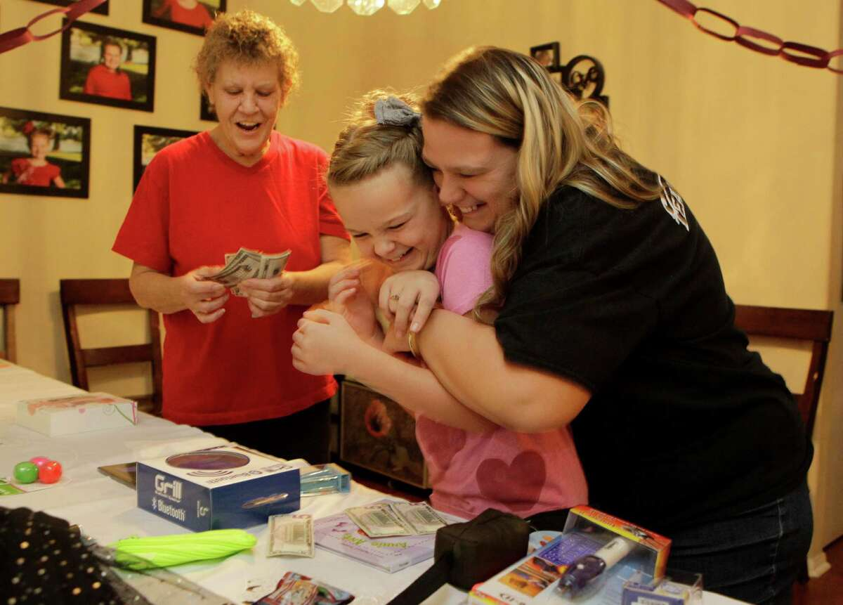 Heather Feagain, hugs her daughter, Grace, 10, as her aunt, Joanne Dumire, left, counts the play money Grace used to purchase Christmas presents Monday, Dec. 21, 2015, in Sugar Land. The items are purchased with Monopoly-like Mama bucks that the children earn for performing chores.