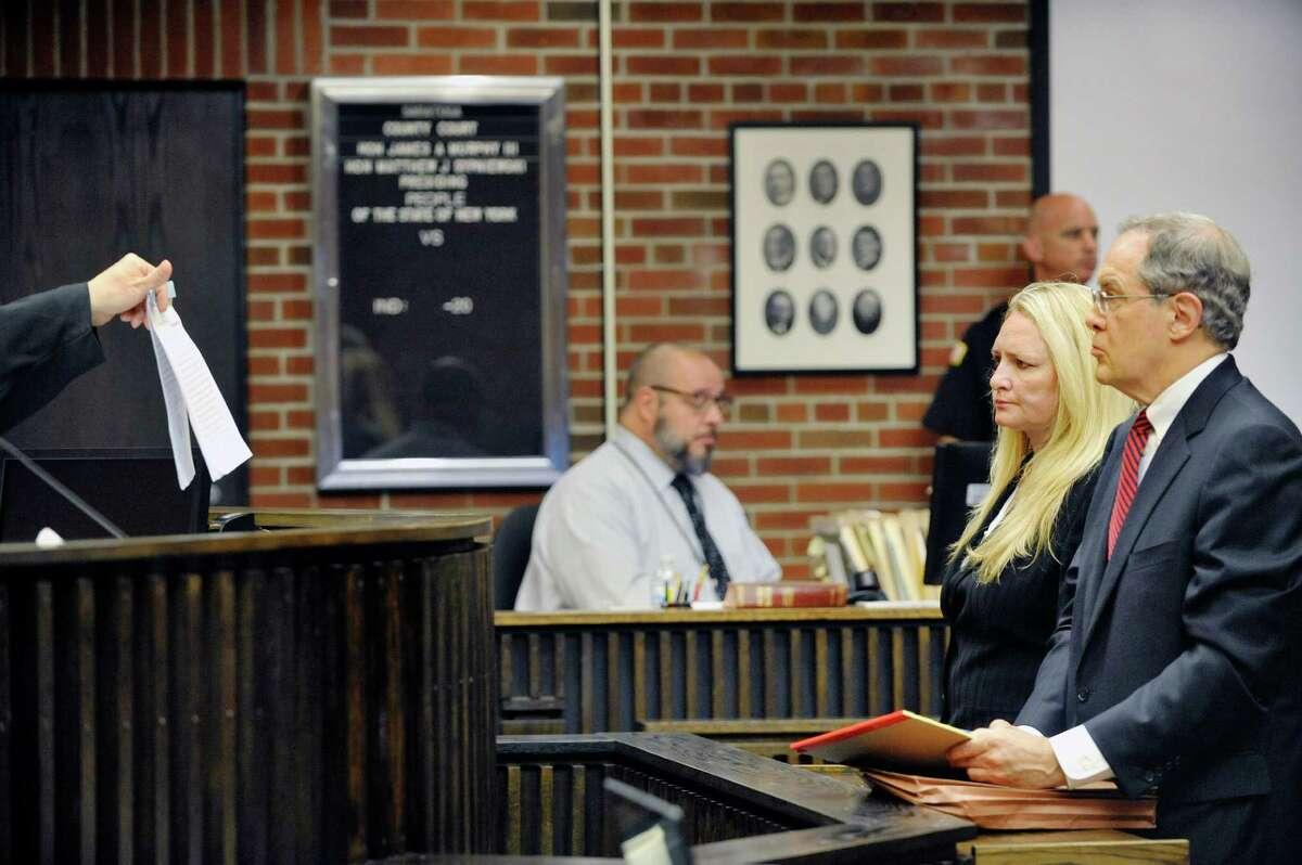 Judge Matt Sypniewski, left, shows the signed plea agreement to Former Halfmoon Supervisor Melinda Wormuth, left, and her attorney E. Stewart Jones Tuesday, Aug. 18, 2015, at Saratoga County Court in Ballston Spa, N.Y. (Paul Buckowski / Times Union)
