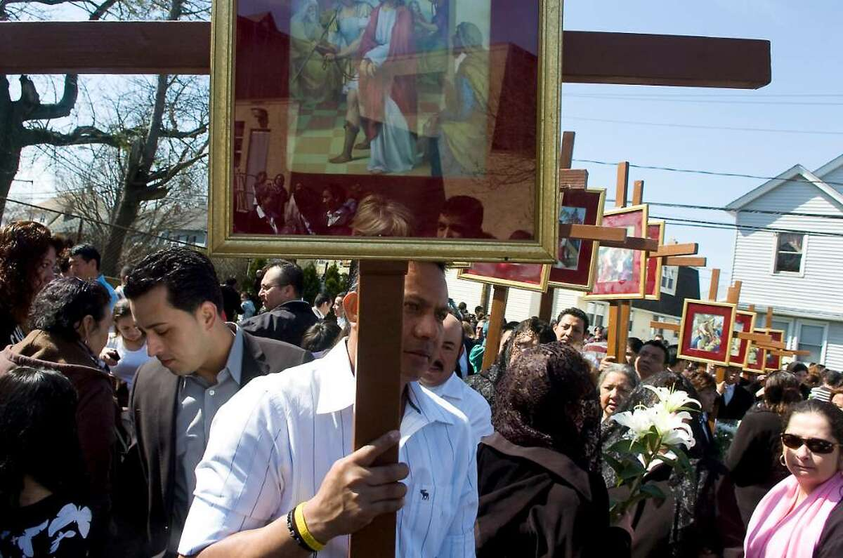 Parishioners and residents process into Our Lady of Montserrat Church at the end of the Good Friday Stations of the Cross procession in Stamford, Conn. on Friday April 2, 2010