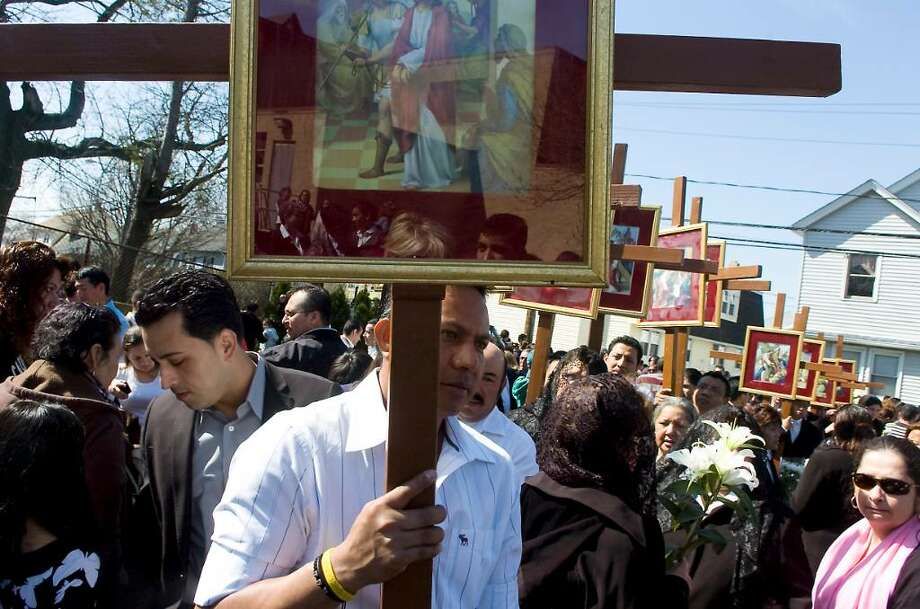 Parishioners and residents process into Our Lady of Montserrat Church at the end of the Good Friday Stations of the Cross procession in Stamford, Conn. on Friday April 2,  2010 Photo: Kathleen O'Rourke / Stamford Advocate