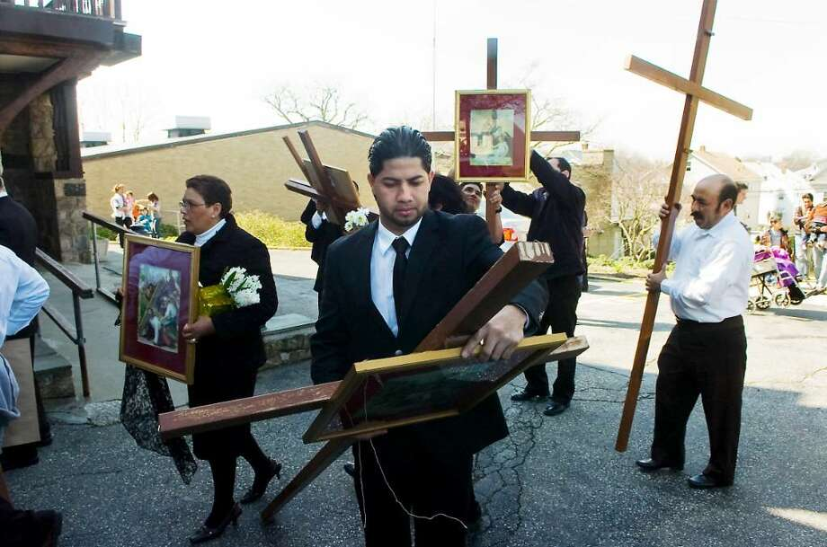 William Saravia removes the seventh station at the end of the Good Friday Stations of the Cross procession from Cummings Beach to Our Lady of Montserrat Church in Stamford, Conn. on Friday April 2,  2010 Photo: Kathleen O'Rourke / Stamford Advocate