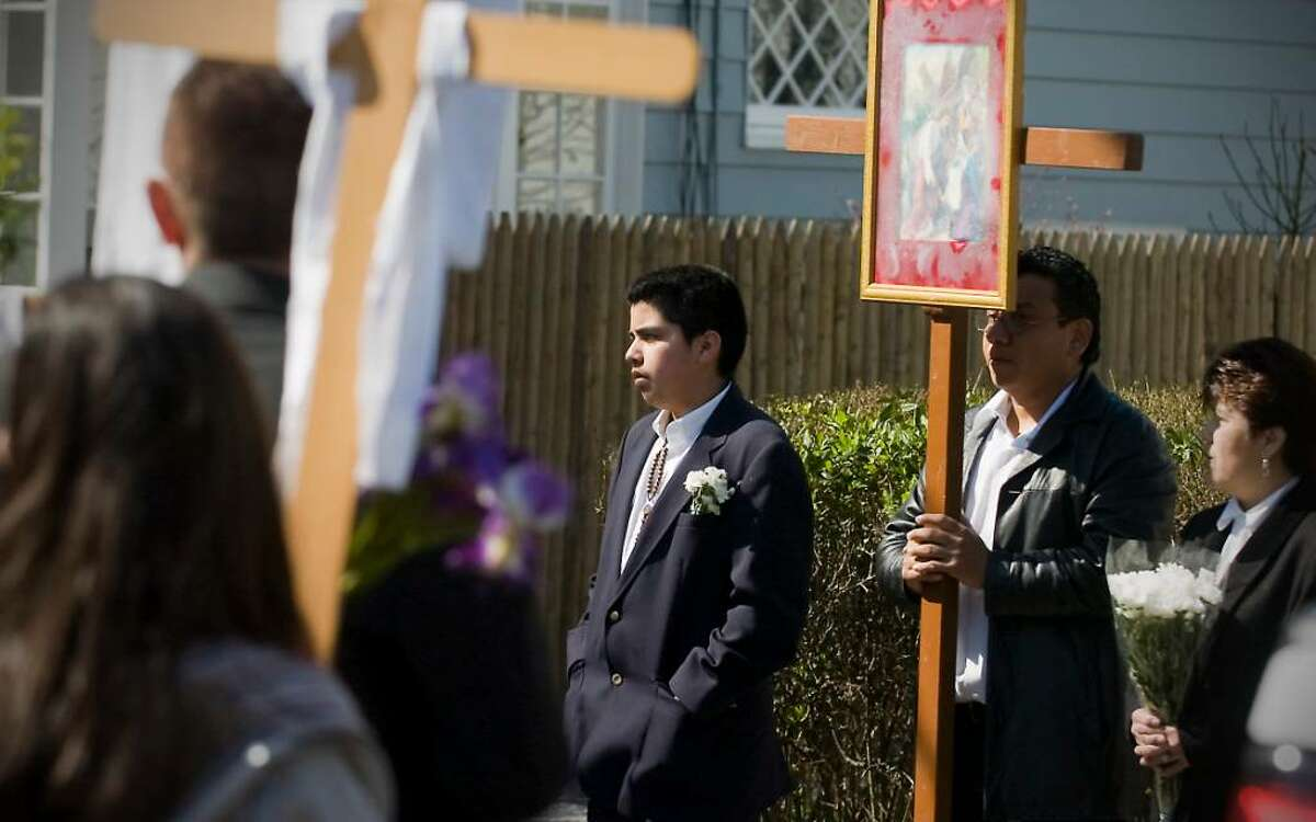 Joseph Barrientos, 13, joins parishioners and residents as they participate in the Good Friday Stations of the Cross procession from Cummings Beach to Our Lady of Montserrat Church in Stamford, Conn. on Friday April 2, 2010