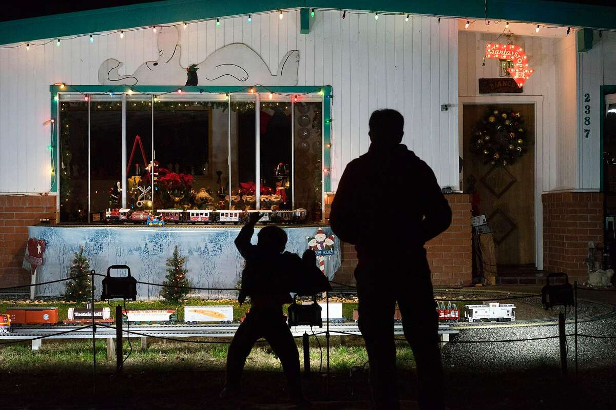 Gavin Bayer, left, and his father James watch John Bianco's train display in Mountain View, Calif on Tuesday, Dec. 22, 2015. The Bianco family has brought together residents of Mountain View and beyond with their annual model train display.