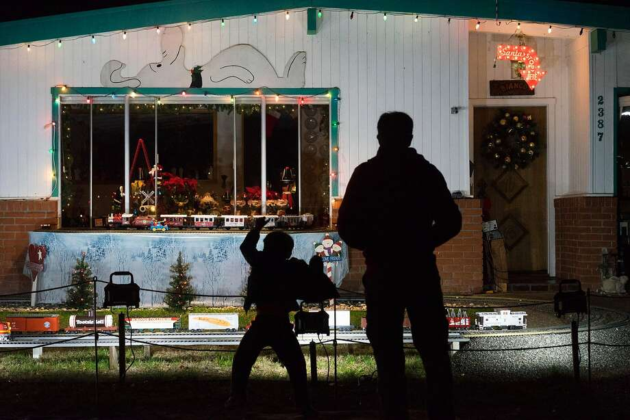 Gavin Bayer, left, and his father James watch John Bianco's train display in Mountain View, Calif on Tuesday, Dec. 22, 2015. The Bianco family has brought together residents of Mountain View and beyond with their annual model train display. Photo: James Tensuan