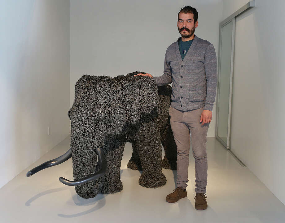 "Ernesto Ibanez poses with his nail and styrofoam sculpture, ""Mammoth"" at the Cinnabar Gallery at the Blue Star Art Complex, Monday, Dec. 14, 2015. Ibanez is part of the exhibition, ""Extraordinary"" which also includes artist, Kevin Box, Javier Venegas and Dorte Weber. It took Ibanez 11 months to make using over 125,000 nails. Photo: JERRY LARA /San Antonio Express-News / © 2015 San Antonio Express-News"