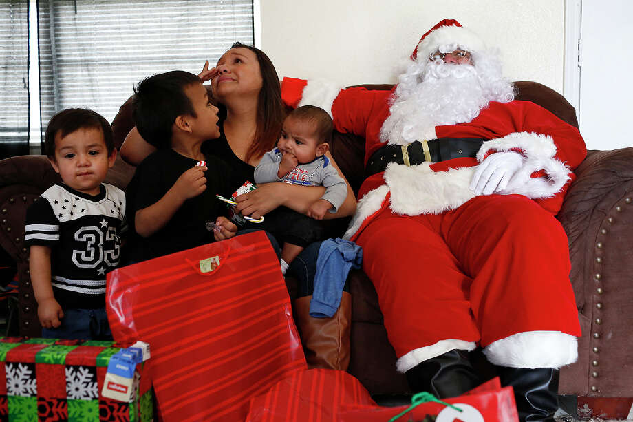 Mona Ayala wipes away tears as she sits with Santa Claus (Robert Cantu III) and her sons, Jayryn Canales, 18 months, from left, Israel Ayala, 4, and Jorge Canales, four months, as the Ghost Town Survivors deliver presents to Ayala and her boys at Cassiano Homes on Monday, Dec. 21, 2015. Photo: Lisa Krantz, STAFF / SAN ANTONIO EXPRESS-NEWS / SAN ANTONIO EXPRESS-NEWS