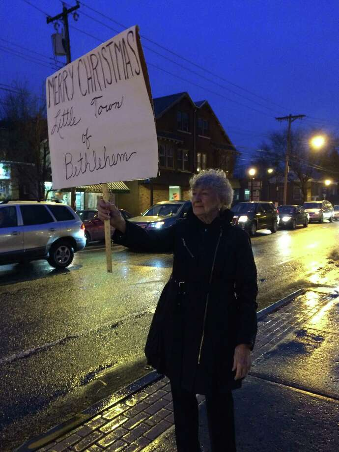 Marcia Wendth carries at sign at the Delmar Four Corners in protest of the town of Bethlehem's decision not to have religious holiday signs at the busy intersection. (Lauren Stanforth / Times Union)
