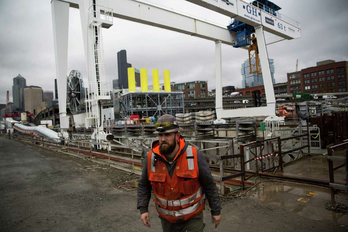A construction worker walks over Bertha's launching pit during a press update event on the Highway 99 tunnel boring machine on Wednesday, Dec. 23, 2015.