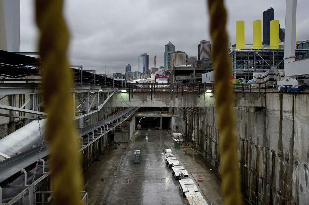 Downtown Seattle is seen in the distance above the launch pit for Bertha, the WSDOT Highway 99 tunnel boring machine, on Wednesday, Dec. 23, 2015.