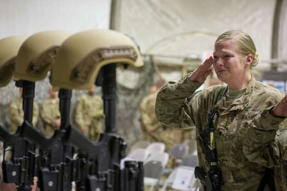 A U.S. service member salutes her fallen comrades Wednesday during a memorial ceremony for the six airmen killed in Monday's suicide attack. The deadliest attack in Afghanistan since 2013 claimed the lives of six U.S. troops, including one from South Texas. Photo: Tech. Sgt. Robert Cloys, HOGP / U.S. Air Force