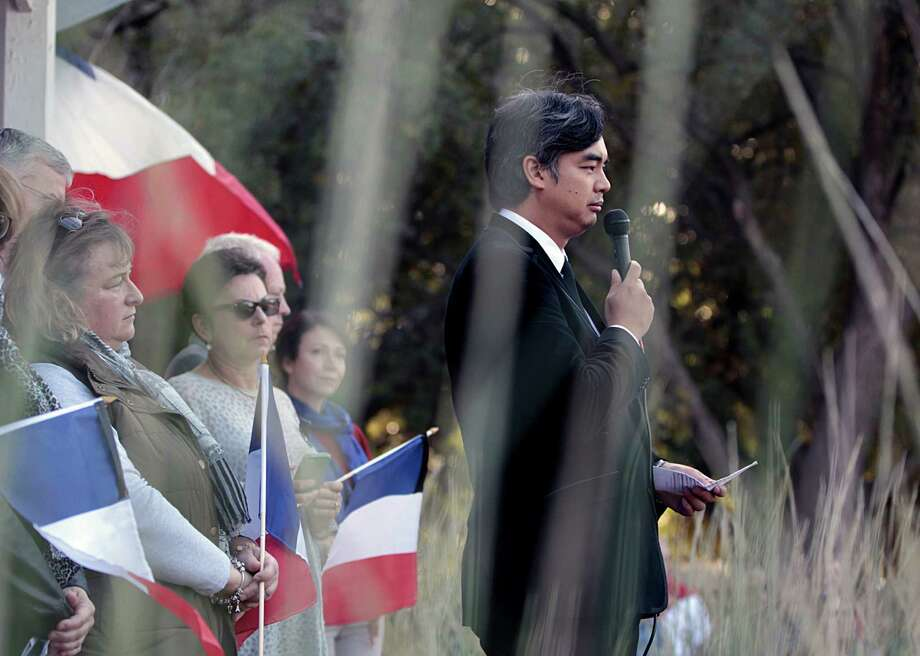 Consulate General of France Sujiro Seam participates in a program at Sam Houston Park in Houston to mourn the the victims of  the Nov. 13 terrorist   attacks in Paris. Photo: James Nielsen, Staff / © 2015  Houston Chronicle