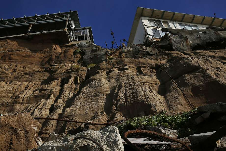 Properties on 330, right, and 320 Esplanade Ave perch on the edge of an eroding cliff with debris below them Dec. 23, 2015 in Pacifica, Calif. Both properties are vacant. Photo: Leah Millis, San Francisco Chronicle