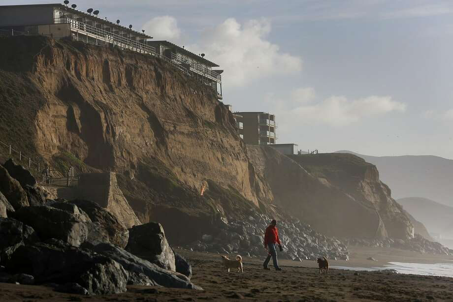 Properties along Esplanade Ave can be seen perched on the edge of an eroding cliff Dec. 23, 2015 in Pacifica, Calif. The center property is vacant. Photo: Leah Millis, San Francisco Chronicle