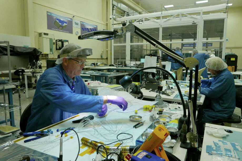 James Foster helps assemble components for satellites at a lab inside the Southwest Research Institute. The San Antonio facility was established seven decades ago by a Yale-educated oilman, Thomas Baker Slick. Photo: Billy Calzada, Staff / San Antonio Express-News
