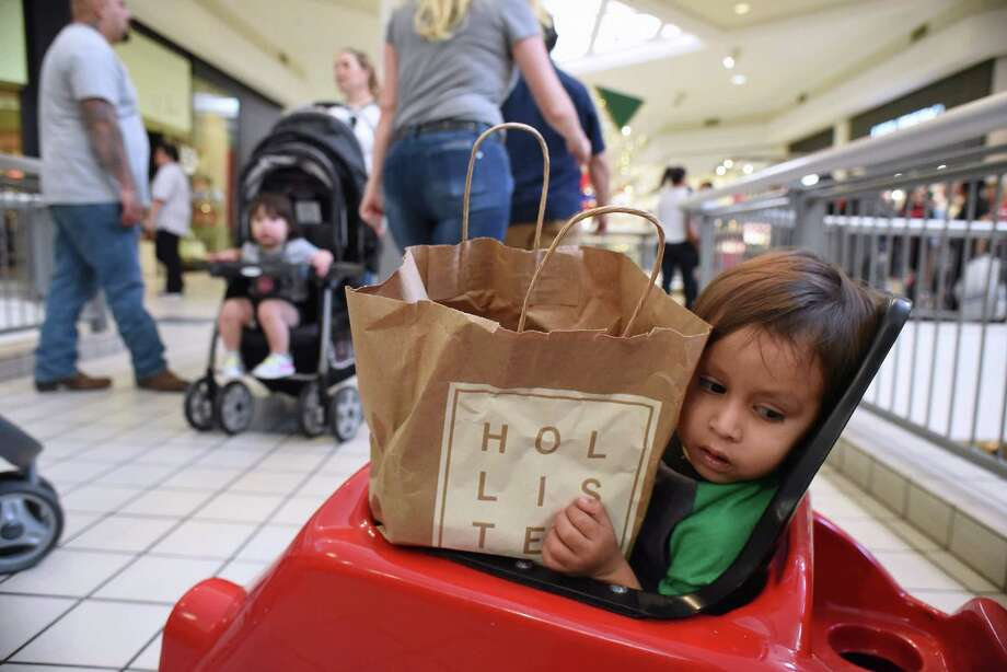 Dennis Ibarra, 2, shares a cart with merchandise as he accompanies his family as they make the rounds in search of last-minute gifts at Ingram Park Mall on Wednesday. Photo: Billy Calzada /San Antonio Express-News / San Antonio Express-News