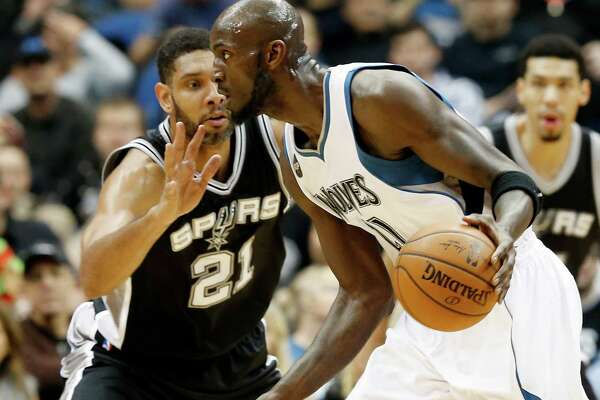 Minnesota Timberwolves' Kevin Garnett, right, drives by San Antonio Spurs' Tim Duncan in the first quarter of an NBA basketball game, Wednesday, Dec. 23, 2015, in Minneapolis. (AP Photo/Jim Mone)