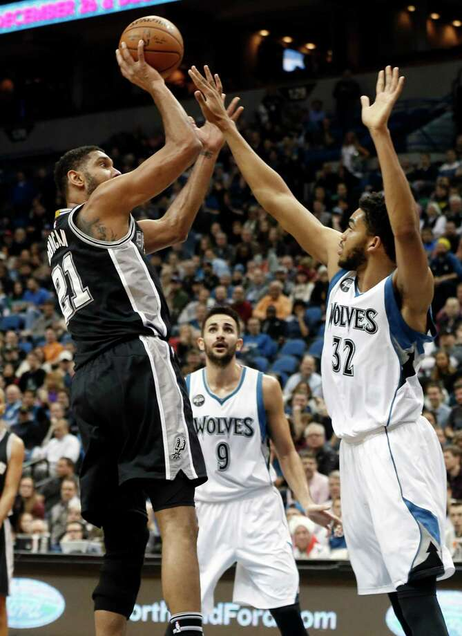 San Antonio Spurs' Tim Duncan, left, shoots as Minnesota Timberwolves' Karl-Anthony Towns defends in the first quarter of an NBA basketball game, Wednesday, Dec. 23, 2015, in Minneapolis. (AP Photo/Jim Mone) Photo: Jim Mone, Associated Press / AP