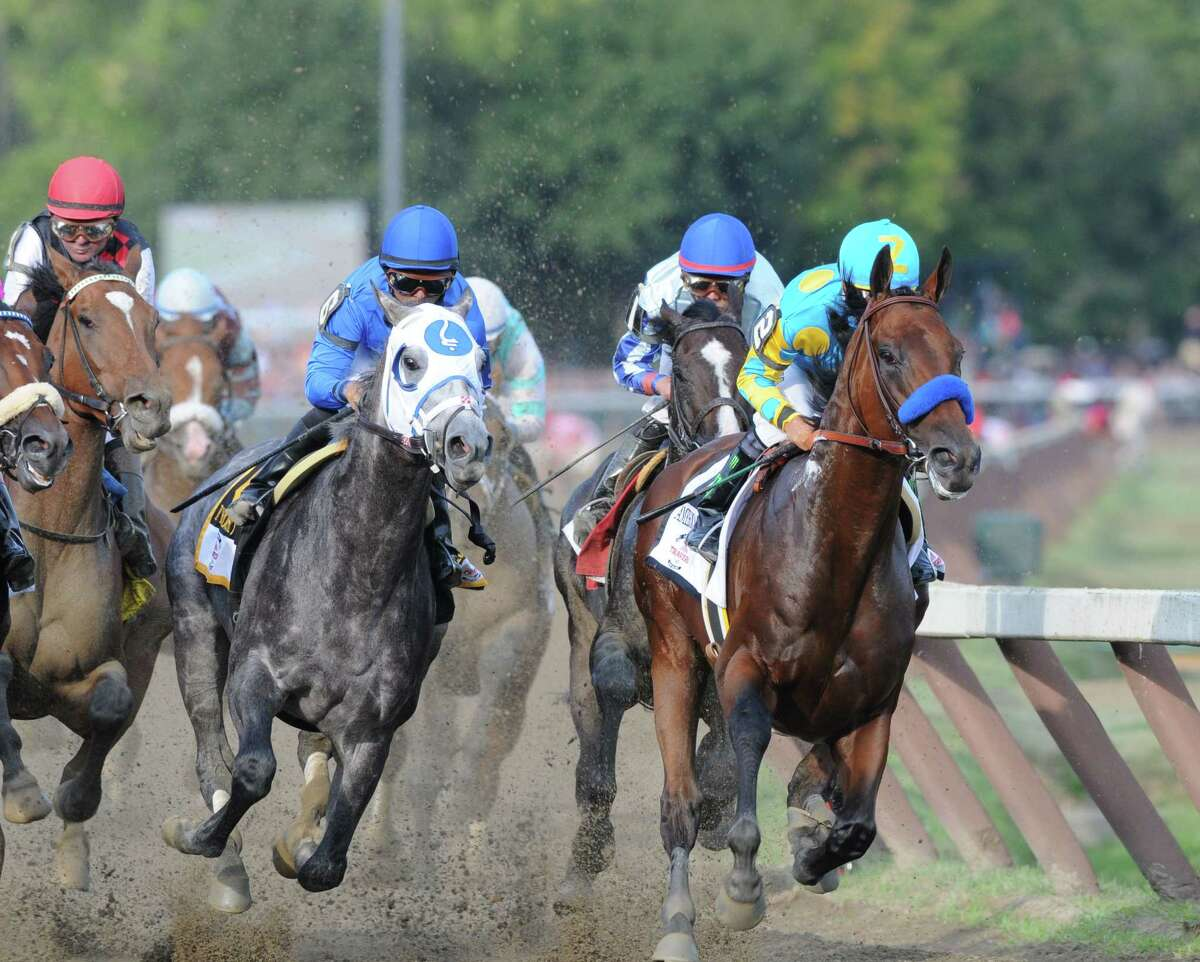 American Pharoah and Victor Espinoza, right, takes an early lead into the Clubhouse turn as Frosted with jockey Joel Rosario, center, challenges during the Travers Stakes at Saratoga Race Course Saturday, Aug. 29, 2015, in Saratoga Springs, N.Y. Keen Ice with Javier Castellano was the winner. (Will Waldron/Times Union)