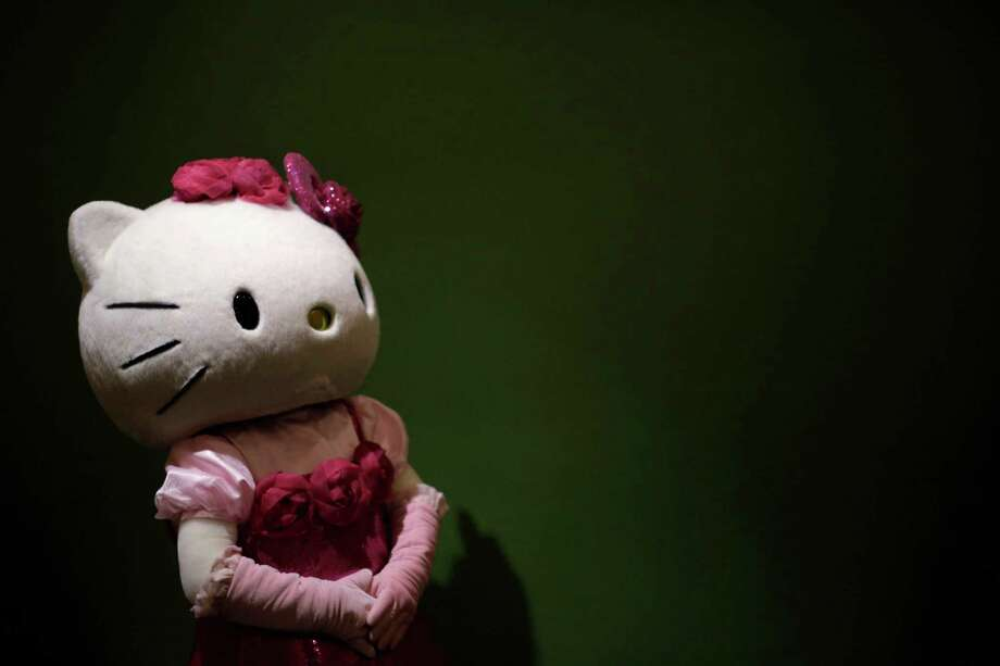 A model dressed as Hello Kitty waits for guests to pose for a souvenir photo at the Sanrio Puroland theme park in Tokyo. Photo: Eugene Hoshiko, STF / AP