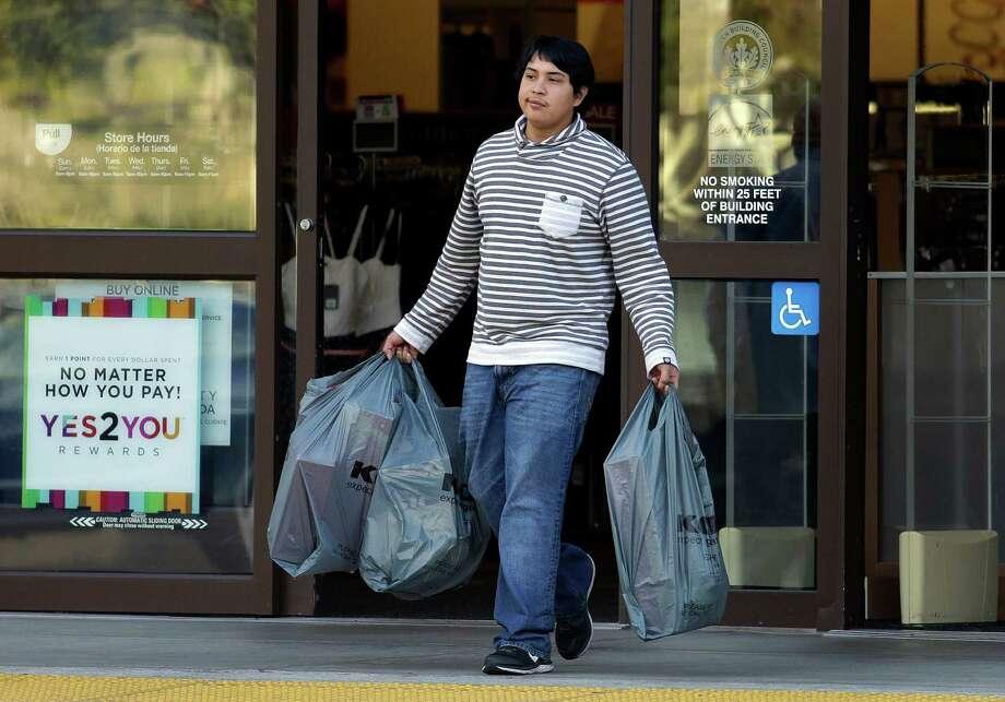 A shopper leaves a store in Alameda, Calif. Consumer spending rebounded in November.  Photo: Ben Margot, STF / AP