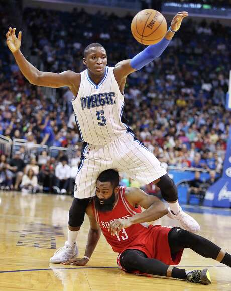 The Magic's Victor Oladipo must look out below for a floored James Harden. Photo: Stephen M. Dowell, MBR / Orlando Sentinel