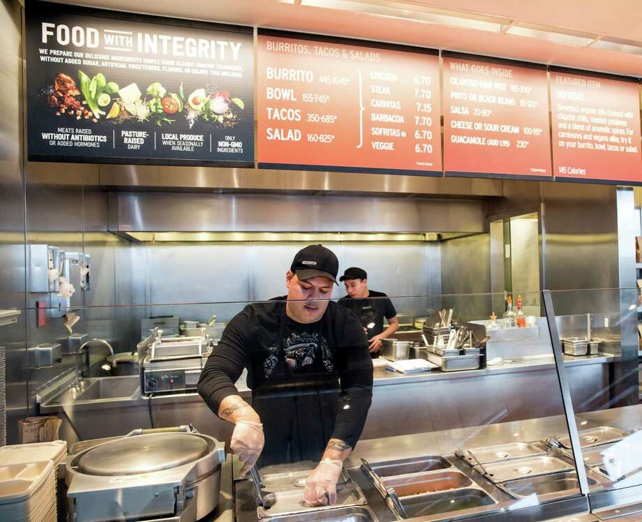 FILE - In this Dec. 15, 2015, file photo, a Chipotle Mexican Grill employee prepares food, in Seattle. After an E. coli outbreak that sickened more than 50 people, Chipotle is changing its cooking methods to prevent the nightmare situation from happening again. (AP Photo/Stephen Brashear, File) Photo: Stephen Brashear, FRE / FR159797 AP