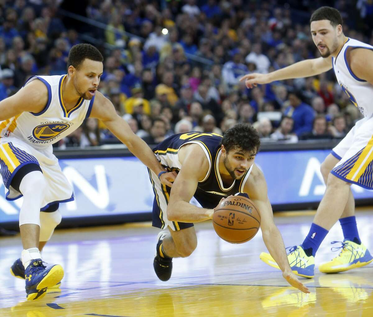 Golden State Warriors' Stephen Curry and Klay Thompson watch as Utah Jazz' Raul Neto falls while dribbling in 2nd quarter during NBA game at Oracle Arena in Oakland, Calif., on Wednesday, December 23, 2015.