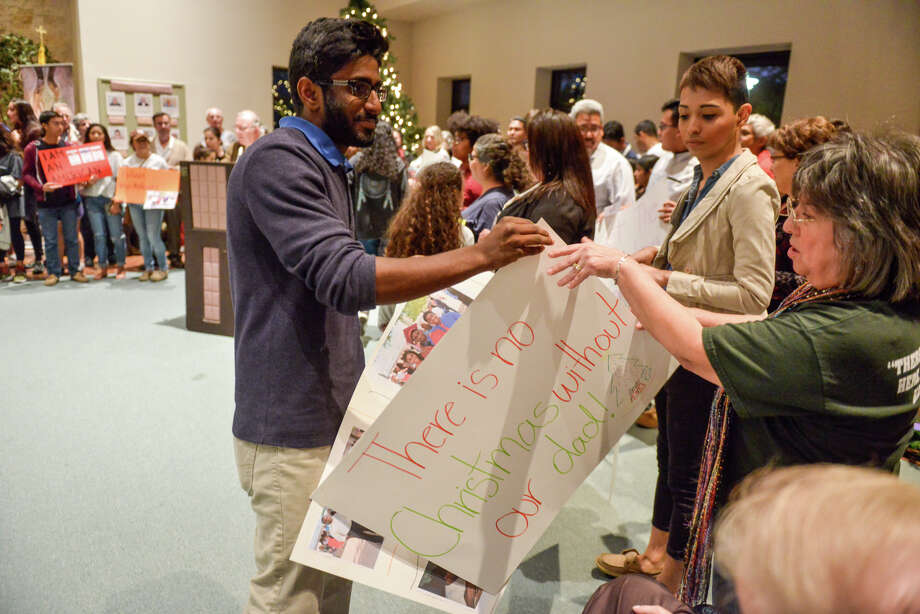 Savi Randeniya hands out posters to supporters during a St. Brigid's Church vigil to protest the deportation proceedings against he and his family. Photo: Photos By Robin Jerstad / For The San Antonio Express-News