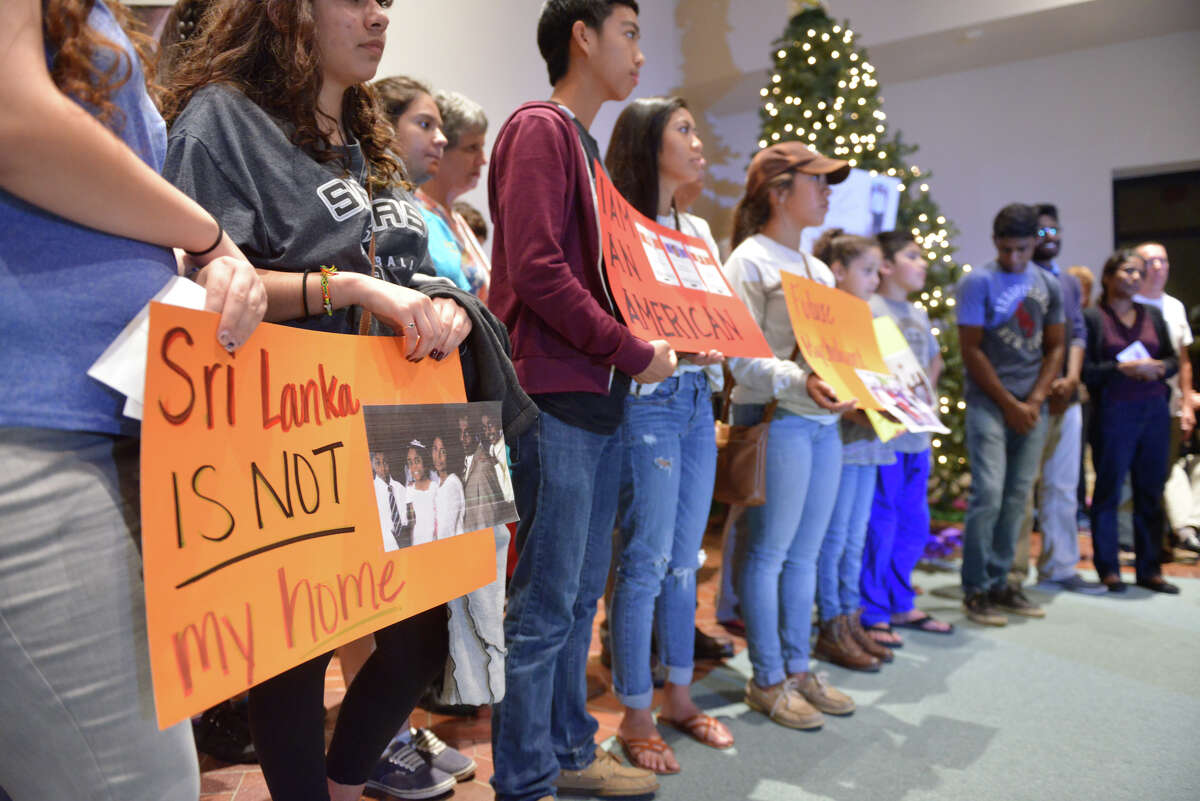Supporters hold signs during a St. Brigids Church vigil against the deprtation proceeding of the family of Saman Rendeniya