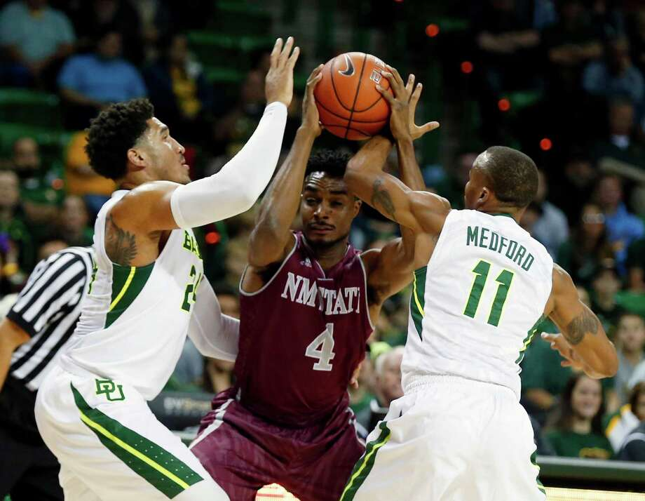 Baylor's Ishmail Wainright, left, and Lester Medford, right, put the defensive clamps on New Mexico State's Ian Baker. Photo: Rod Aydelotte, FRE / FRE36102AP