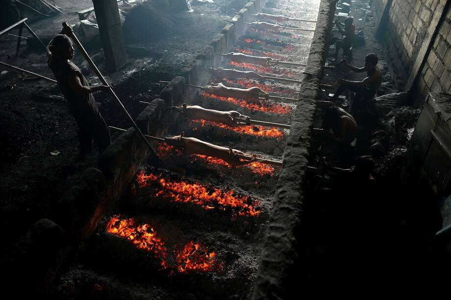 "A worker (L) applies oil onto bamboo skewered pigs as his colleagues rotate them while they are roasted over hot coals in Manila on December 23, 2015. ""Lechon"", or roasted pig, has always been regular fare at Philippine festivities, especially during Christmas and New Year celebrations. The Philippine Christmas season runs from December until the second week of January.  Photo: Noel Celis, AFP / Getty Images"