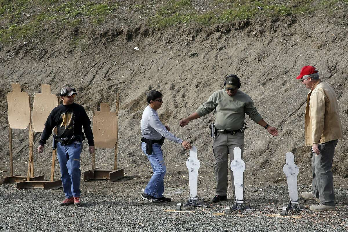 Members (l to r) Ray Bala, Jun Bayla, Manuel Newman and Range Officer Tom Scocca reset the targets during an Action Pistol practice event at the Richmond Rod and Gun Club in Richmond, Calif., on Saturday December 12, 2015.