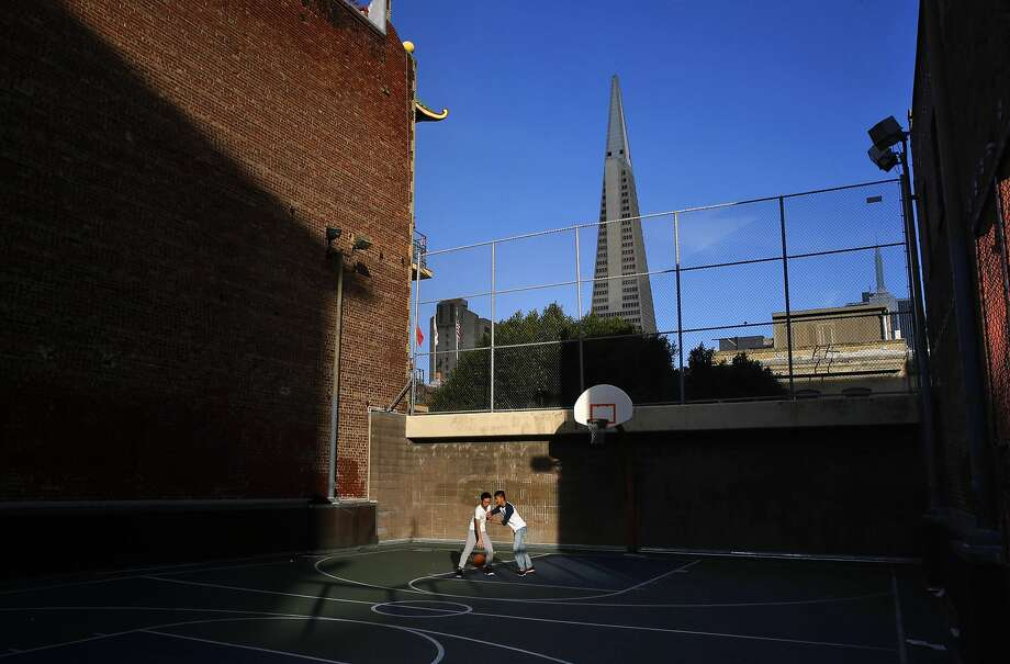 """Above: Children shoot hoops at Chinatown's Willie """"Woo Woo"""" Wong Playground, which is to get a $6 million make over in 2018. Below: Rosa Chen, who grew up in Chinatown, and Gordon Chin talk on the playground. Photo: Michael Macor, The Chronicle"""