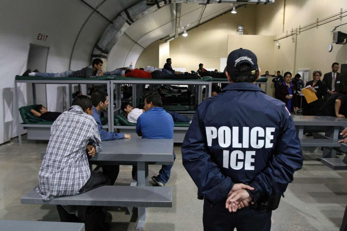 FILE - An Immigration and Customs Enforcement (ICE) officer guards a group of 116 Salvadorean immigrants that wait to be deported,at Willacy Detention facility in Raymondville, Texas on December 18, 2008 early morning. The Willacy facility is used by the US Immigration and Customs Enforcement agency (ICE) to keep illegal immigrants in detention before they are deported. Today, 116 Salvadorean nationals --83 men and 33 women-- were woken up at 4 a.m. and transported in buses under strict surveillance to Harlengen's airport to be taken back to El Salvador. AFP PHOTO/ Jose CABEZAS (Photo credit should read Jose CABEZAS/AFP/Getty Images)