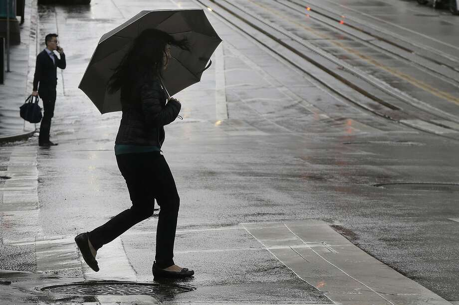 A woman carries an umbrella as she crosses California Street in San Francisco, Tuesday, Dec. 22, 2015.The Bay Area is expected to have a wet and cool Christmas Eve, forecasters said Thursday. Photo: Jeff Chiu, Associated Press