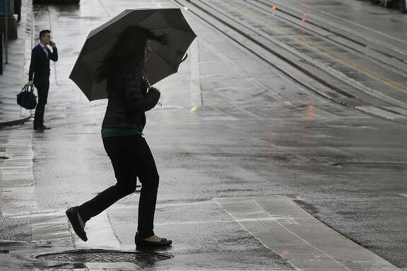A woman carries an umbrella as she crosses California Street in San Francisco. A series of storms was set to soak the Bay Area all week. (AP Photo/Jeff Chiu)
