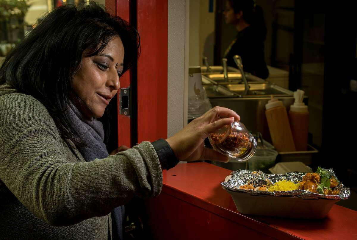 Owner Binita Pradhan sprinkles chili flakes onto the combo plate at Bini's Kitchen in the S.F. Financial District.