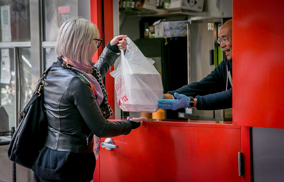 Danny Cruz gives a woman her to-go order at Bini's Kitchen in the S.F. Financial District.