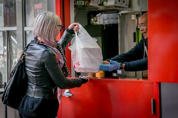 Danny Cruz gives a woman her food to go at Bini's Kitchen in San Francisco, Calif., on December 23rd, 2015.