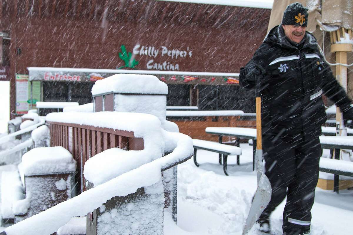 In this photo provided by Northstar California Resort, a worker walks past heavy snowfall on the deck of the Lodge at Big Springs Monday, Dec. 21, 2015, in Truckee, Calif. Winter storm warnings were posted Monday in the Sierra Nevada after the National Weather Service predicted heavy mountain snow during the holiday week. A storm moving into the northern Sierra was expected to drop more than an inch of snow an hour at times. (Northstar California Resort via AP)