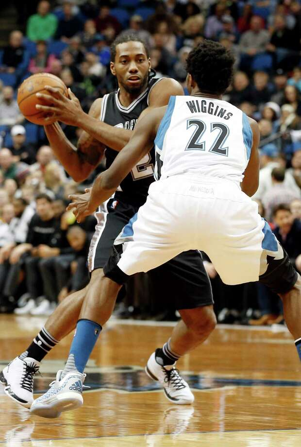 San Antonio Spurs' Kawhi Leonard, left, looks for space around Minnesota Timberwolves' Andrew Wiggins in the first quarter of an NBA basketball game, Wednesday, Dec. 23, 2015, in Minneapolis. Leonard led the Spurs with 19 points in their 108-83. (AP Photo/Jim Mone) Photo: Jim Mone / Associated Press / AP
