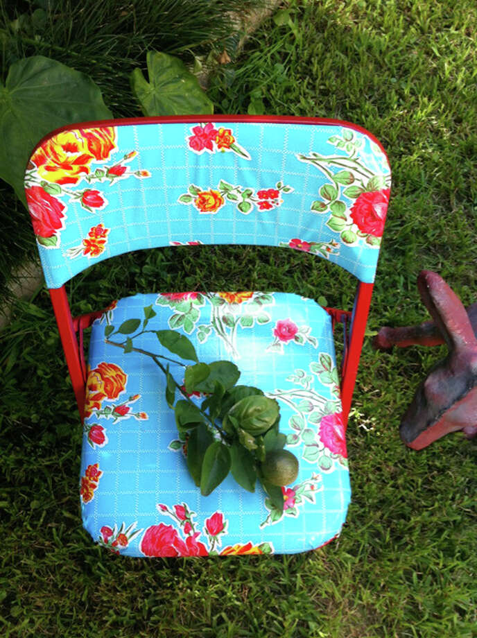 Mexican oil cloth and spray paint can turn thrift-store folding chairs into colorful patio furniture. Photo: Anjelica Cazares